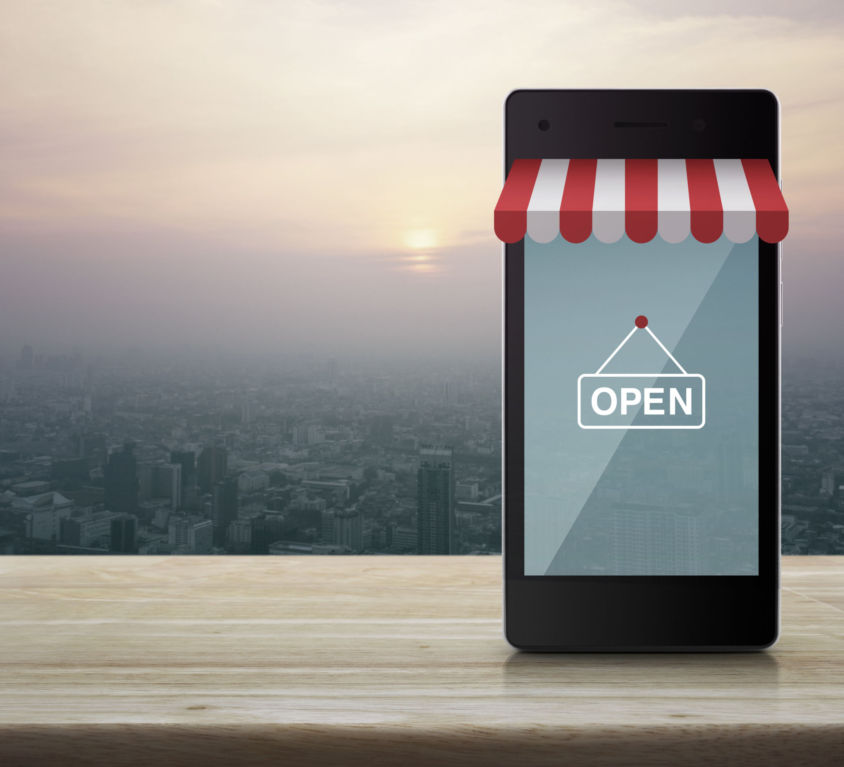 Modern smart mobile phone with on line shopping store graphic and open sign on wooden table over city tower at sunset, vintage style, Shop online concept
