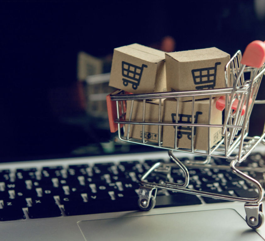 Shopping online concept - Parcel or Paper cartons with a shopping cart logo in a trolley on a laptop keyboard. Shopping service on The online web. offers home delivery..